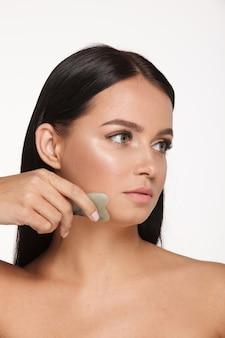 Piękna dziewczyna z naturalnym makijażem i czystą skórą. trzyma w ręku jadeitowy peeling do twarzy na wyszczuplenie i przeciwdziałanie efektom starzenia