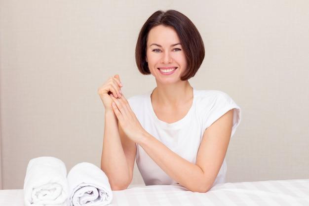 Piękna dziewczyna z otwartym uśmiechem, mistrz masażystka, pracownik salonu piękności, siedzący obok kanapy z białymi rolkami ręczników.