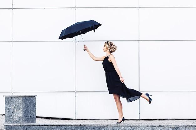 Piękna dziewczyna z parasolem wieje wiatr.