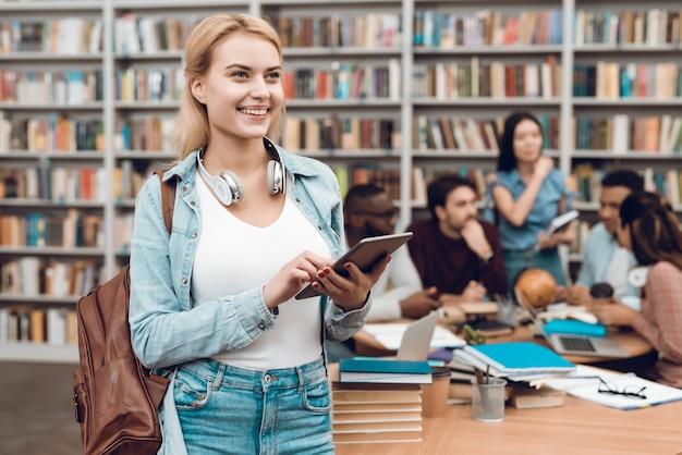 Piękna dziewczyna z pastylką w bibliotece.