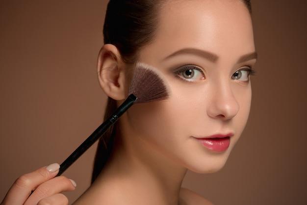 Piękna dziewczyna z pędzlem do makijażu. idealna skóra. nakładanie makijażu
