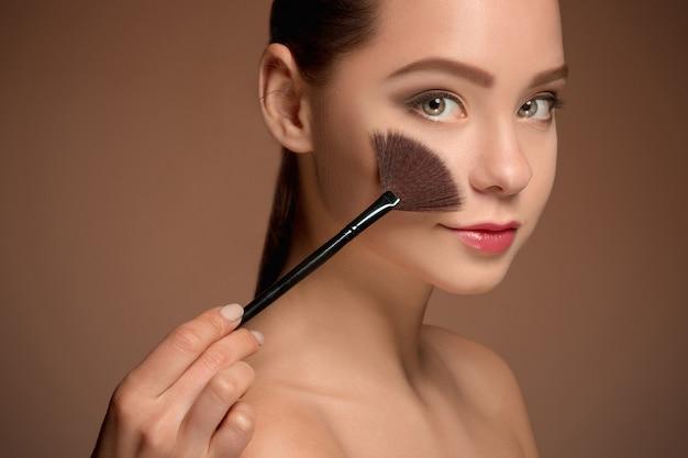 Piękna dziewczyna z pędzlem do makijażu. idealna skóra. stosowanie makijażu