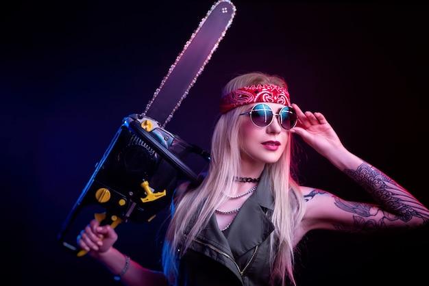 Piękna dziewczyna z piłą łańcuchową na czarnym tle w neonowym świetle