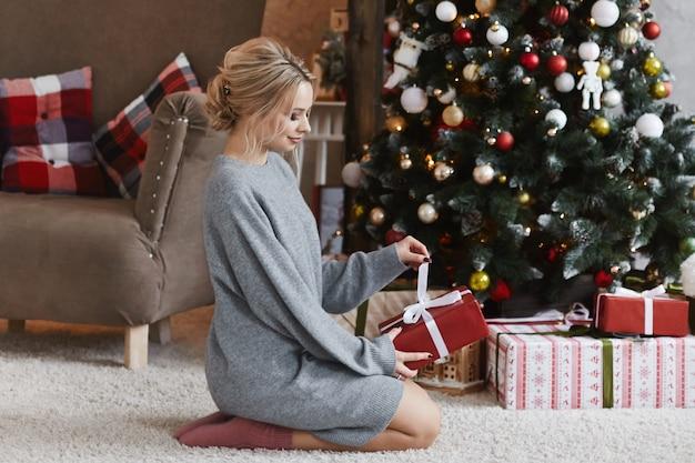 Piękna dziewczyna z platynowym blond włosami w sukience z dzianiny siedzi z prezentem świątecznym na podłodze