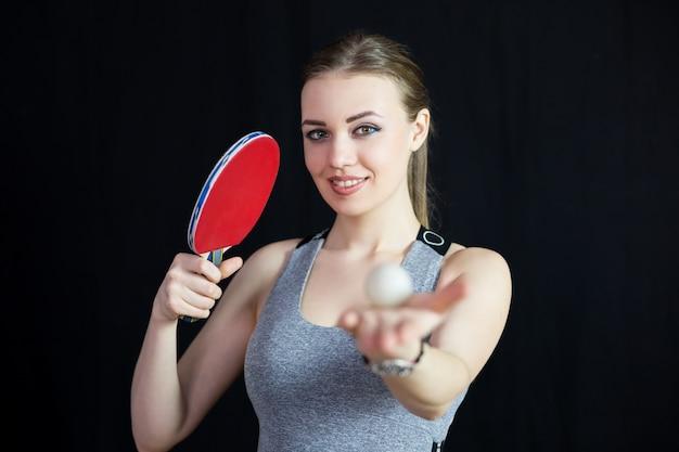 Piękna dziewczyna z rakietą tenisową i piłką.