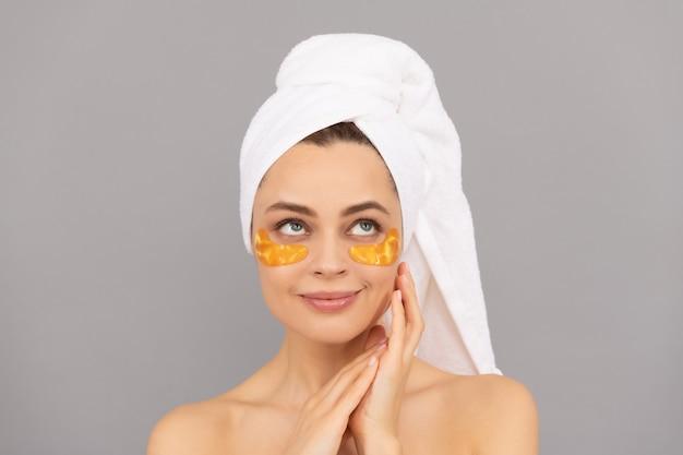 Piękna dziewczyna z ręcznikiem frotte użyj złotej opaski na oczy dla skóry, zdrowej skóry.