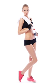 Piękna dziewczyna z ręcznikiem i butelką wody