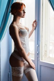 Piękna dziewczyna z redhair w bieliźnie pozuje obok okna