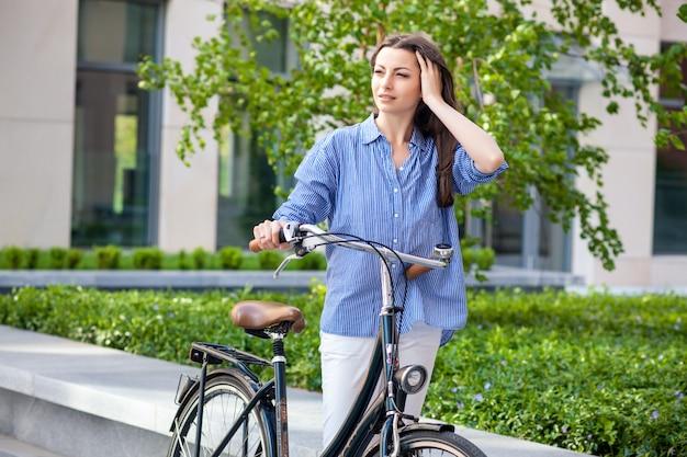 Piękna dziewczyna z rowerem na drodze