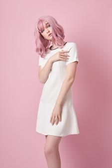 Piękna dziewczyna z różowymi włosami, farbowanie włosów. śliczna kobieta z anime stoi na różowym tle w krótkiej białej sukience. kolorowe włosy, idealna fryzura