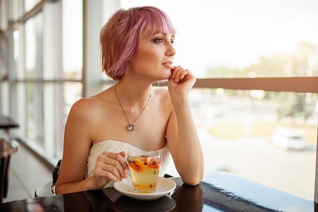Piękna dziewczyna z różowymi włosami malowanymi siedzi w restauracji przy oknie, pijąc herbatę owocową