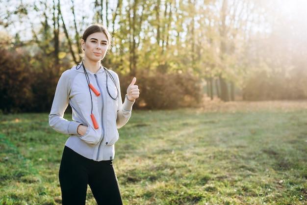 Piękna dziewczyna z skakanką na ramieniu outdoors pokazuje kciuk up.