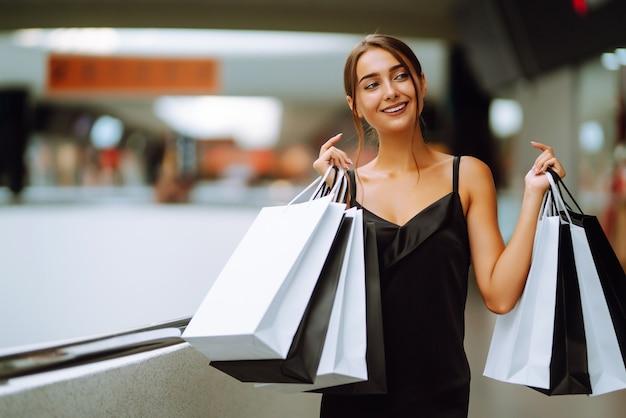 Piękna dziewczyna z torby na zakupy patrząc na kamery i uśmiechając się robiąc zakupy w centrum handlowym