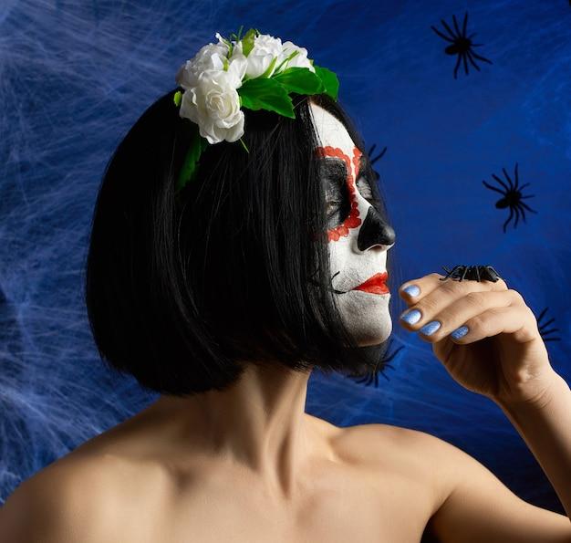 Piękna dziewczyna z tradycyjną meksykańską maską śmierci. calavera catrina