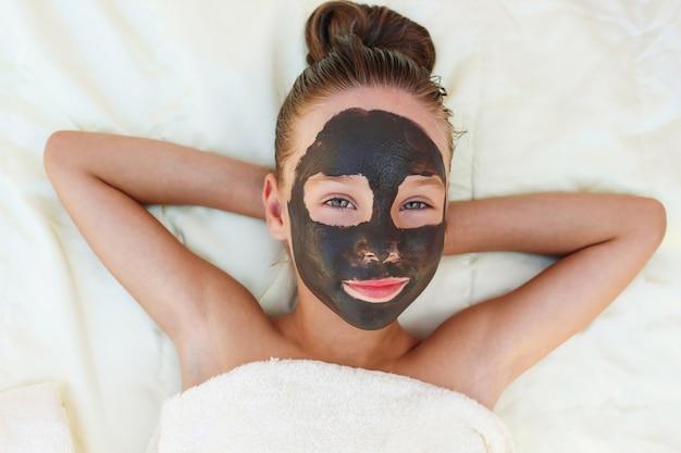 Piękna dziewczyna z twarzową czarną gliny maską.