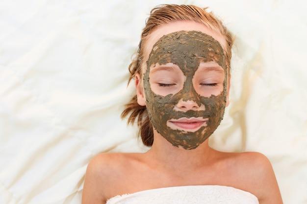 Piękna dziewczyna z twarzy gliny maską.