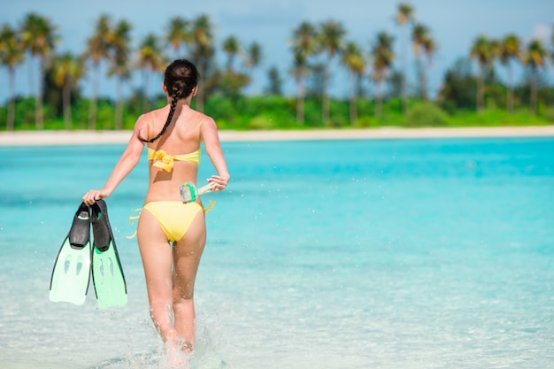 Piękna dziewczyna z wyposażeniem na wielkich kamieniach przygotowywających dla snorkeling