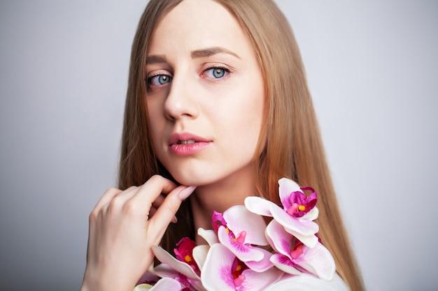 Piękna dziewczyna z zdrowej skóry i gałęzi orchidei