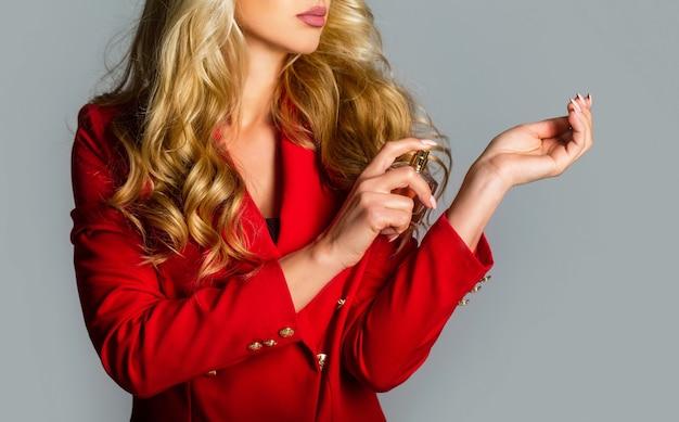 Piękna dziewczyna za pomocą perfum. kobieta z butelką perfum. perfumy butelka kobieta zapach w sprayu. kobieta trzyma butelkę perfum. kobieta prezentuje zapach perfum.