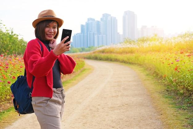Piękna dziewczyna za pomocą telefonu komórkowego w parku kwiatowym na tle budynku