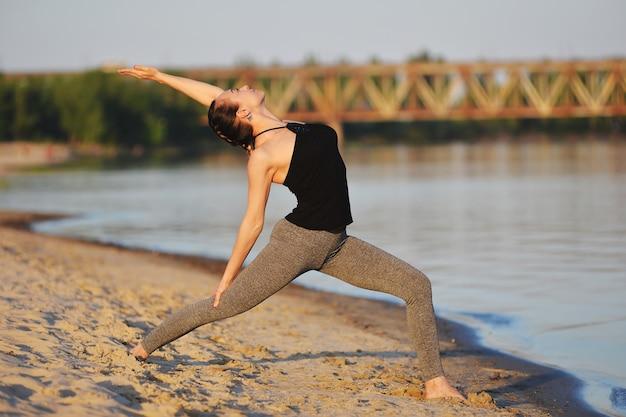 Piękna dziewczyna zaangażowana w jogę na plaży wiosną