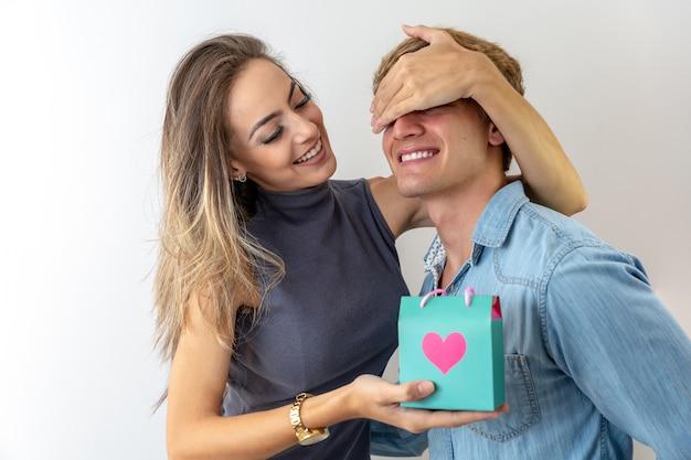 Piękna dziewczyna zakrywa oczy chłopaka i daje mu prezent, na szarym tle