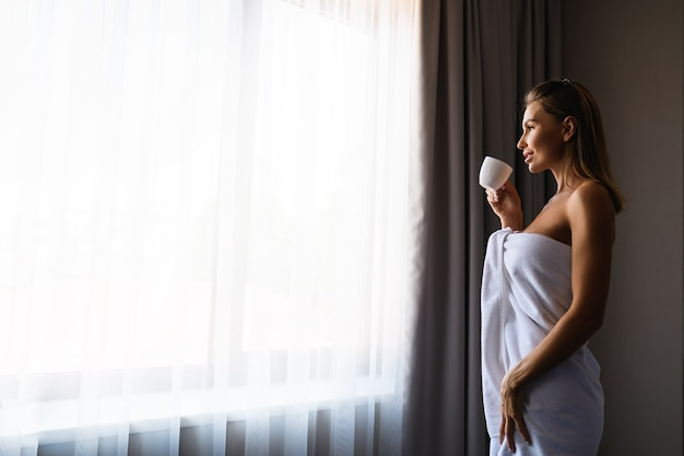Piękna dziewczyna zatrzymać się w pobliżu okna owiniętego białym ręcznikiem, wypić drinka w małej filiżance.