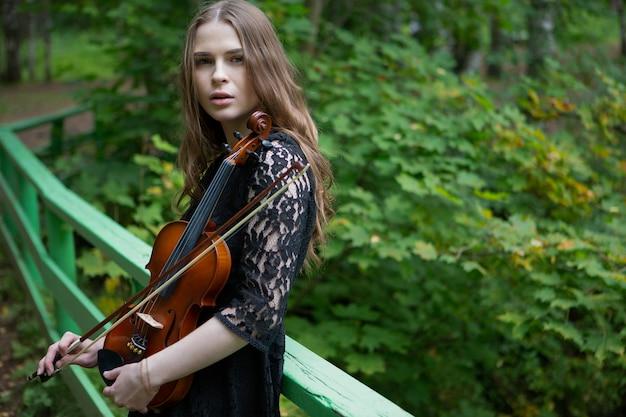 Piękna dziewczyna ze skrzypcami w dłoniach na moście