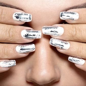 Piękna dziewczyna ze srebrnymi metalowymi paznokciami.