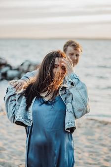 Piękna dziewczyna ze swoim chłopakiem spaceruje po plaży. długie włosy powiewające na wietrze.