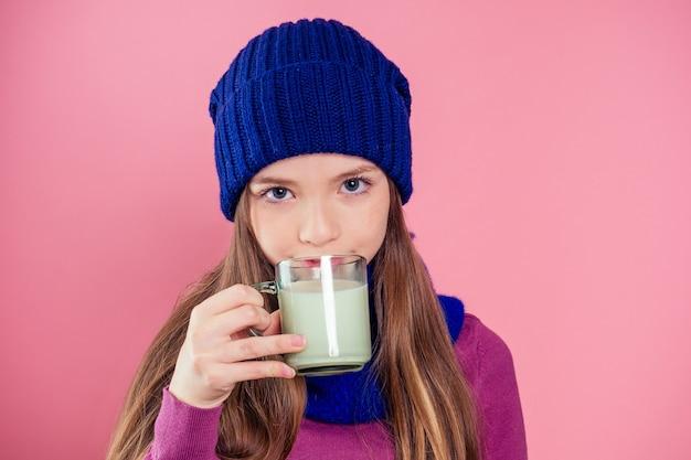 Piękna dziewczyna ze szklanką mleka w czapce z dzianiny w studio na różowym tle. szczęśliwe dziecko dziewczynka pije jogurt noc bożego narodzenia