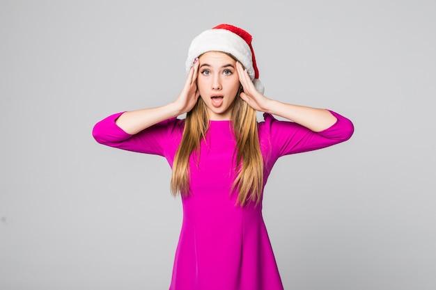 Piękna dziewczyna ze złotymi włosami w różowej sukience i kapeluszu noworocznym nieoczekiwana sytuacja na białym tle