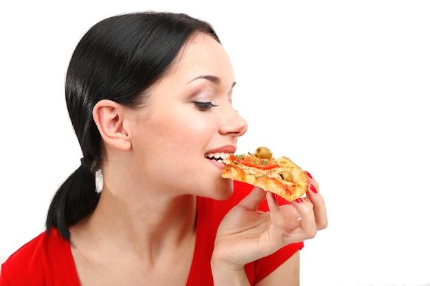 Piękna dziewczyna zjada pizzę z bliska na białym tle