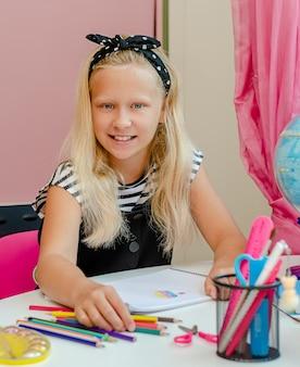 Piękna dziewczynka kaukaski siedzi przy biurku i uśmiecha się. koncepcja uczenia się