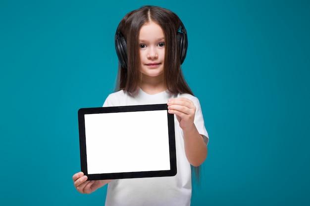 Piękna dziewczynka w koszulkę i słuchawki z długimi włosami trzymać tablet