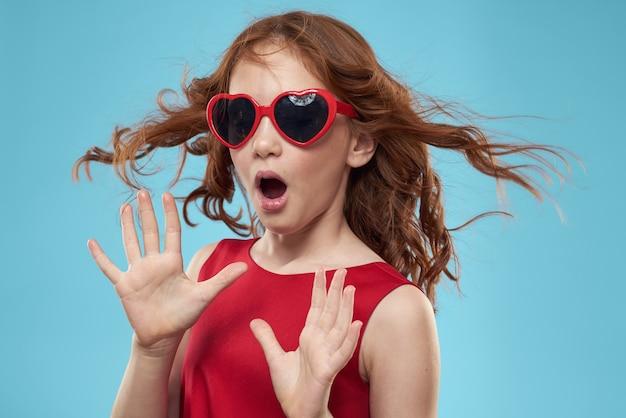 Piękna dziewczynka w okularach serca i czerwonej sukience, księżniczka, słodkie dziecko w studio na niebieskim tle