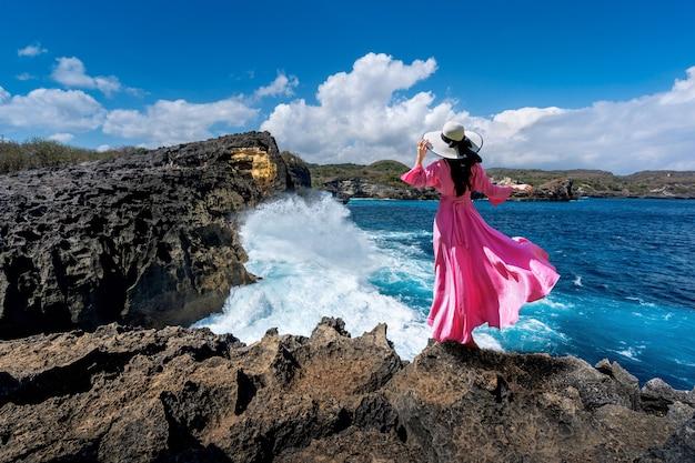 Piękna dziewczyny pozycja na skale przy anioła billabong blisko łamającej plaży w nusa penida wyspie, bali w indonezja.