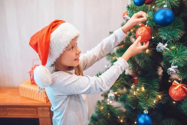 Piękna dziewczyny pozycja przy choinką i ubierać ona z kolorowymi zabawkami. obiema rękami trzyma czerwony. dziewczyna nosi świąteczny kapelusz. ona jest sama w pokoju.