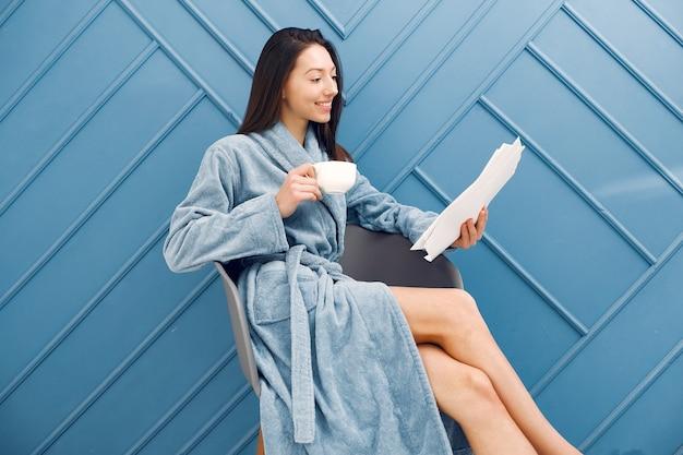 Piękna dziewczyny pozycja w studiu w błękitnym szlafroku