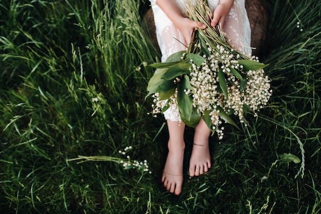 Piękna dziewięcioletnia blondynka w długiej białej sukni z bukietem konwalii, zbliżenie dziewczynki trzymającej kwiaty doliny. lato, zachód słońca.