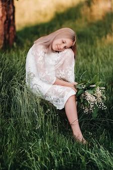 Piękna dziewięcioletnia blondynka z długimi włosami w długiej białej sukni, trzymająca bukiet konwalii, siedzi na kamieniu w parku.lato, zachód słońca.