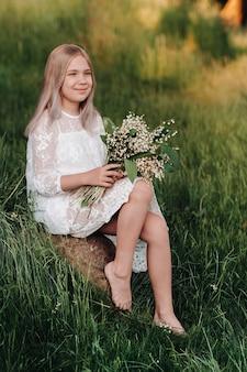 Piękna dziewięcioletnia blondynka z długimi włosami w długiej białej sukni, trzymająca bukiet kwiatów konwalii, spacerująca wśród natury w parku. lato, zachód słońca.