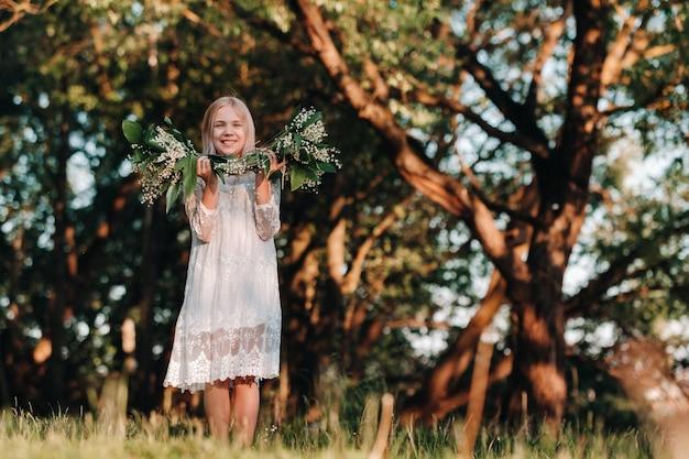 Piękna dziewięcioletnia blondynka z długimi włosami w długiej białej sukni, trzymająca bukiet kwiatów konwalii, spacerująca wśród przyrody w parku. lato, zachód słońca.