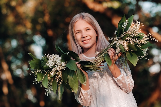 Piękna dziewięcioletnia blondynka z długimi włosami w długiej białej sukni, trzymająca bukiet kwiatów konwalii, spacery na łonie natury w parku.lato, zachód słońca.