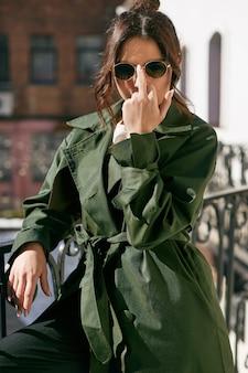 Piękna elegancka brunetki kobieta jest ubranym zielonego żakiet na balkonie