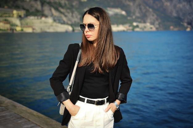 Piękna elegancka dama z brązowymi kręconymi włosami i okularami nad jeziorem garda limone. podróżuj po włoszech.