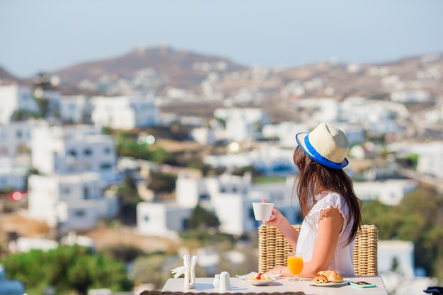 Piękna elegancka dziewczyna ma śniadanie w kawiarni na świeżym powietrzu z niesamowitym widokiem na miasto mykonos.