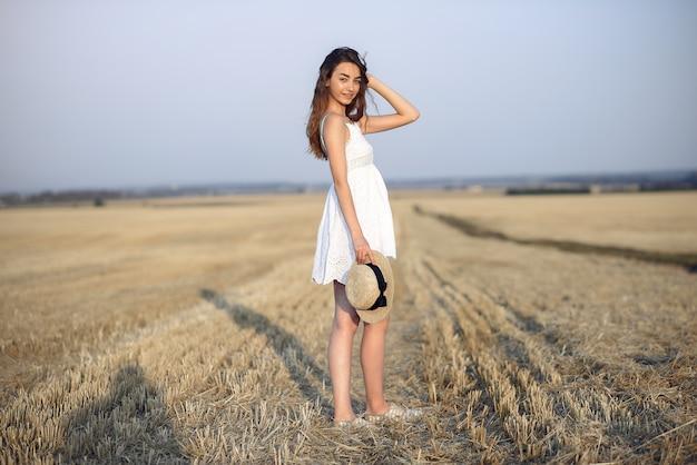 Piękna elegancka dziewczyna w polu pszenicy jesienią