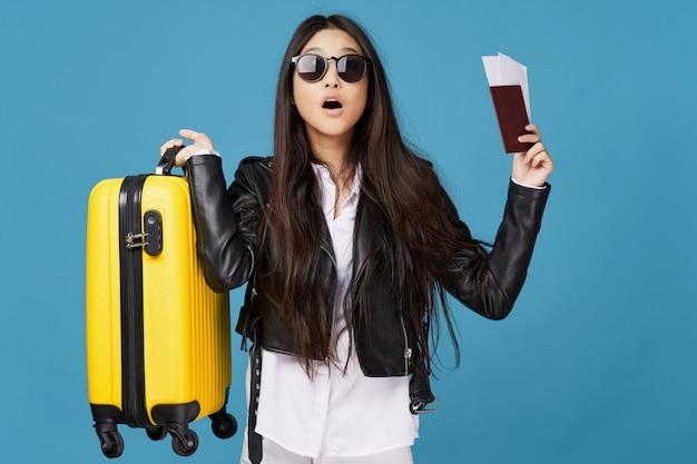 Piękna elegancka kobieta nosi ciemne okulary i trzyma paszport i walizkę
