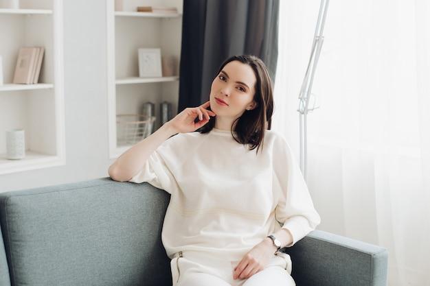 Piękna elegancka kobieta w biały relaksować na kanapie.